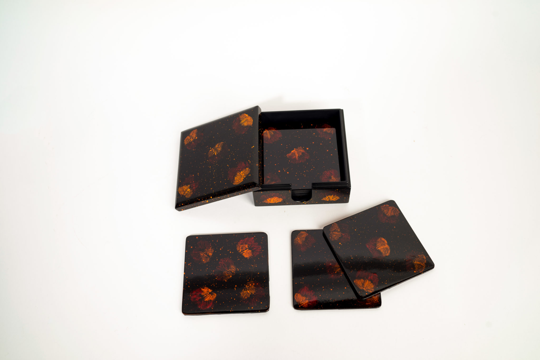 Set of eight pressed flower wooden lacquer coasters and matching wooden lacquer box showing lid removed.