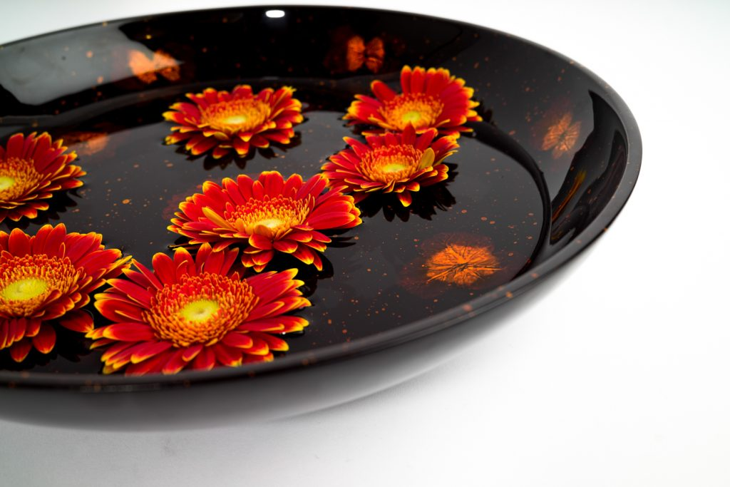 image showing how a Silkwood Traders wooden lacquer bowl can be used for floating flower heads in water as a decorative table centrepiece